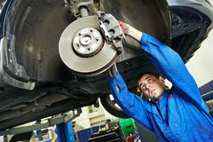 Auto mechanic at car brake shoes examining Royalty Free Stock Photo