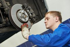 Auto mechanic at car brake shoes eximining. Car mechanic examining car wheel brake disc and shoes of lifted automobile at repair service station Stock Images