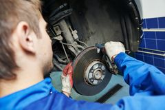 Auto mechanic at car brake shoes eximining. Car mechanic examining car wheel brake disc and shoes of lifted automobile at repair service station Stock Photography
