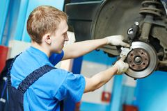 Auto mechanic at car brake shoes replacement. Car mechanic replacing car wheel brake shoes of lifted automobile at repair service station Stock Photography