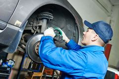 Auto mechanic at car brakes repairing Royalty Free Stock Images