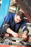 Auto mechanic at car engine repair work. Car mechanic examining car engine of automobile at repair service station royalty free stock images