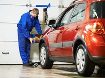 Auto mechanic at car headlight checkup. Car mechanic inspecting headlight lamp of automobile at repair service station stock photos