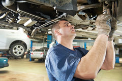 Auto mechanic at car suspension repair work. Car mechanic examining car suspension of lifted automobile at repair service station royalty free stock photo