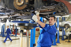 Auto mechanic at car suspension repair work. Car mechanic with spanner tighten car suspension detail of lifted automobile at repair service station Royalty Free Stock Image