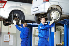 Auto mechanic at car suspension repair work. Car mechanic inspecting car wheel and suspension detail of lifted automobile at repair service station Royalty Free Stock Photo