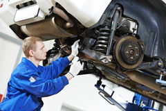 Auto mechanic at car suspension repair work. Car mechanic inspecting car wheel and suspension detail of lifted automobile at repair service station Royalty Free Stock Images