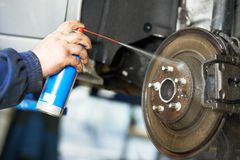 Auto mechanic at car suspension repair work. Car mechanic cleaning car wheel brake disk from rust corrosion at automobile repair service station Stock Images