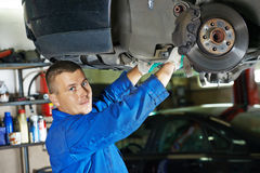 Auto mechanic at car suspension repairing Stock Photography