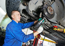 Auto mechanic at car suspension repairing Stock Photo