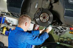 Auto mechanic at car suspension repairing Royalty Free Stock Photos