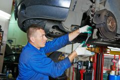 Auto mechanic at car suspension repairing Royalty Free Stock Photo