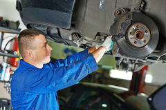 Auto mechanic at car suspension repairing Stock Image