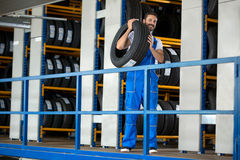 Auto mechanic carrying tire Stock Photography