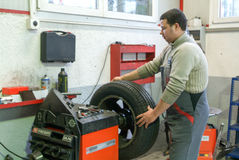 Auto mechanic changes a tire on his garage Stock Photography