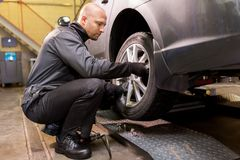 Auto mechanic changing car tire at workshop Royalty Free Stock Photo