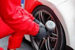 Auto mechanic changing car wheel Royalty Free Stock Photos