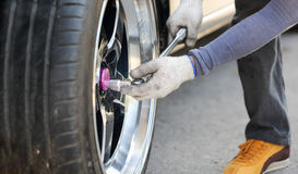 Auto mechanic changing car wheel Royalty Free Stock Images
