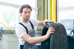 Auto mechanic changing tire in car workshop Stock Photography
