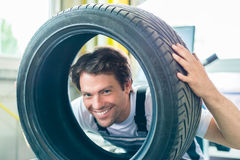 Auto mechanic changing tire in car workshop Stock Image