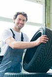 Auto mechanic changing tire in car workshop Royalty Free Stock Image