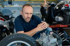 Auto mechanic changing tire with manual tool in epair garage stock photos