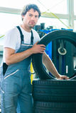 Auto mechanic changing tire in workshop Stock Photos