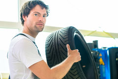 Auto mechanic changing tire in workshop Stock Photo