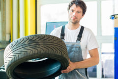Auto mechanic changing tire in workshop Stock Image