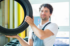 Auto mechanic changing tire in workshop Stock Photography