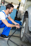 Auto mechanic changing tyre on car Royalty Free Stock Images