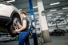 Mechanic adjusting tire wheel at repair garage. Auto mechanic changing wheels tires Inside garage Stock Photos