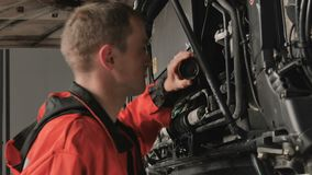 Auto mechanic check something under hood of truck. Auto mechanic checks something under hood of truck. Worker in protective overalls comes to opened hood and stock video footage