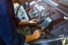 Auto mechanic checking car battery voltage. Hands of mechanic working on car engine in auto repair shop stock images