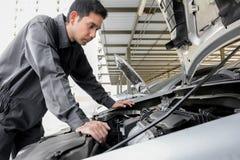 Auto mechanic checking car engine Stock Photo