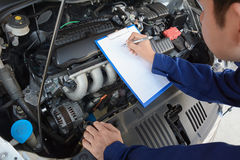 Auto mechanic checking car engine Stock Photos