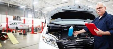 Auto mechanic checking engine. Stock Photos