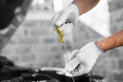 Auto mechanic checking the oil level in car engine Royalty Free Stock Images