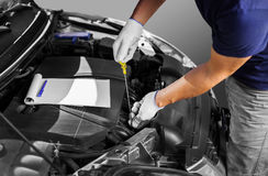 Auto mechanic checking the oil level in car engine Stock Photography