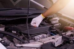 Auto mechanic checking the oil level engine,Maintenance car repair automotive Stock Photography