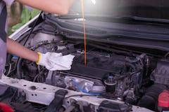Auto mechanic checking the oil level engine,Maintenance car repair automotive Stock Images