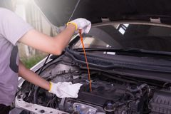 Auto mechanic checking the oil level engine,Maintenance car repair automotive Royalty Free Stock Images
