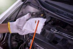 Auto mechanic checking the oil level engine,Maintenance car repair automotive Royalty Free Stock Photo
