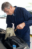 Auto Mechanic Checking Oil Royalty Free Stock Image