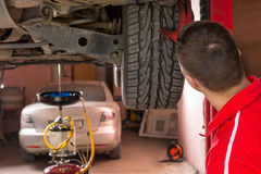 Auto mechanic checking the suspension on a car. Standing under an elevated sedan holding on to a rear wheel as he peers at the undercarriage in a workshop stock photography