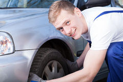 Auto mechanic checks a car tire Stock Photography