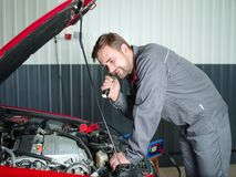The auto mechanic checks the car under the hood. The mechanic in a work suit with a flashlight looks under the hood. Close-up of an auto mechanic under the hood Stock Photo