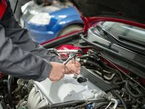 The auto mechanic checks the car under the hood. The mechanic in the working suit twists the bolts on the motor. Close-up of an auto mechanic under the hood Royalty Free Stock Photos