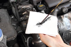 Auto mechanic checks the oil level Royalty Free Stock Photos