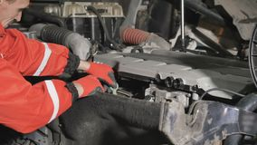 Auto mechanic checks the oil level in engine of truck. Auto mechanic checks the oil level inside the motor of truck. Man in protective orange overalls put the stock video